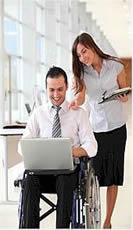 Photo of man in wheelchair and woman with laptops